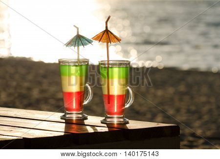 Glasses with multi-colored cocktails on a wooden table in the sun the beach and the sea in the background