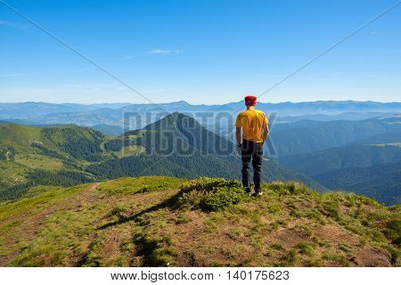 Resting hiker looking into the distance from the top of the mountain. Ukrainian Carpathians. Marmarosy