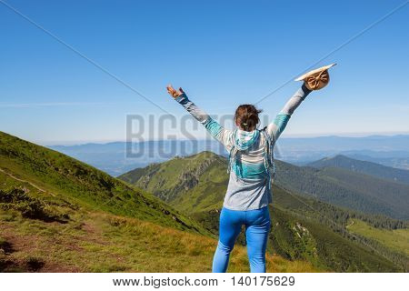 Woman hiker enjoys life standing high in the mountains his arms outstretched. Trekking in the Ukrainian Carpathians