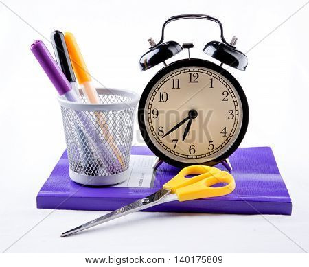 Collection of colorful school supplies with alarm clock over a white background