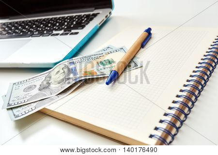 Close up of money on a notepad with a pen. Freelance desktop with accessories. Business workspace in home or office.