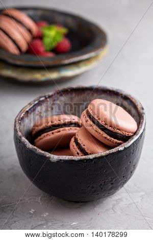 Chocolate french macarons with ganache filling in a black bowl
