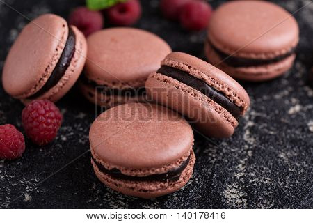 Chocolate and raspberry french macarons with ganache filling on a black table