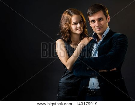 The Russian girl in black skin-tight dress hugging a guy in a velvet jacket