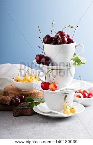 Fresh sweet cherries in white ceramic cups