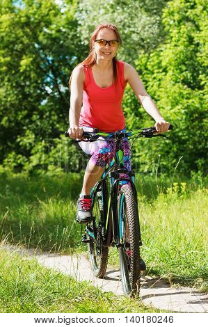 Sports Woman Rides A Bike Outdoors