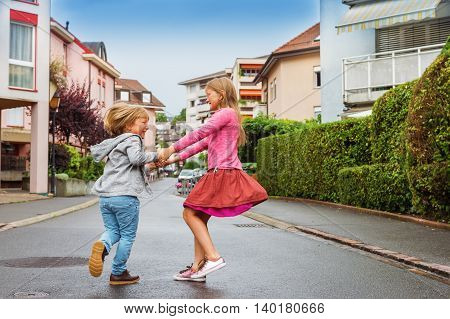 Adorable kids having fun outdoors, dancing on the street