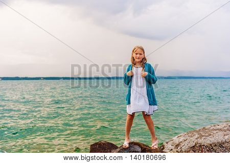 Adorable little girl of 8-9 years old playing by the lake, wearing sandals, dress and blue knitted jacket