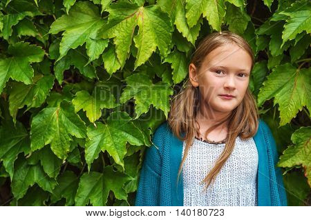Outdoor close up portrait of a cute little girl of 8-9 years old against ivy wall