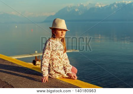 Sunset portrait of adorable little girl sitting next to lake with closed eyes and smile on her face, wearing a hat and beautiful dress
