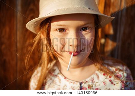 Close up portrait of a cute little girl of 6-7 years old with lollipop at sunset