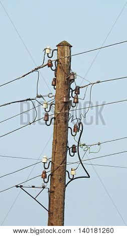 One old wooden electric pole with a lot of wires