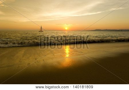 Sailing is a sailboat moving along the water as the sun sets on the horizon and reflects brightly off the the beach side sand.
