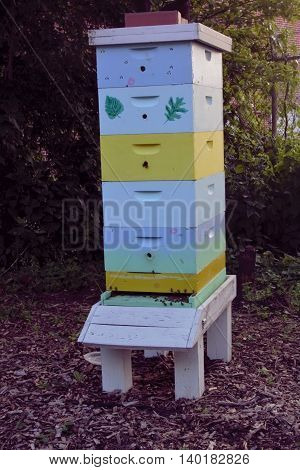 A large wooden, colorful, active bee house