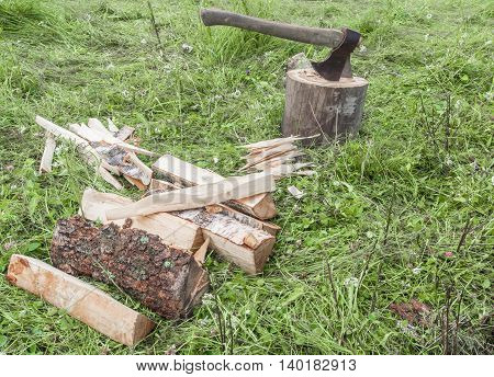Cut logs firewood and old axe. Renewable resource of a energy. Environmental concept.