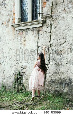 Beautiful little girl in dress and wreath on fairy rope wooden stairs near building wall with window outdoor