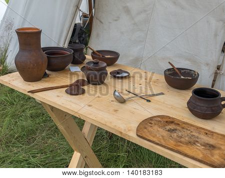 Ancient wooden and clay dishes left on the table after dinner. Outdoor picnic
