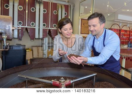 Man and woman looking at coffee beans
