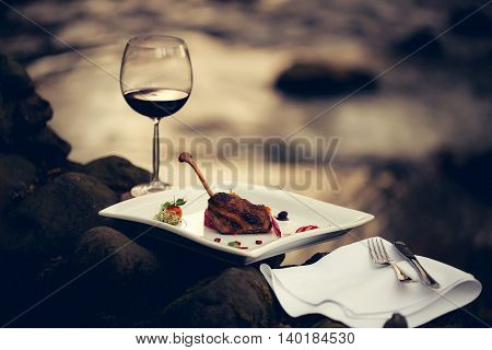 Picnic near water decorated meat with lemon glass of wine served food