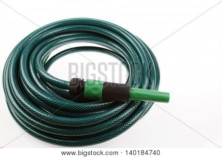 Garden hose coiled on plain background