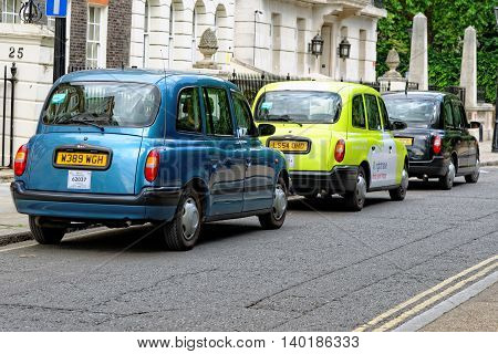 LONDON UK - JULY 1 2014: A row of taxis on a central street in London. Motorized hackney cabs in the UK are known as black cabs although they are now produced in a variety of colours.