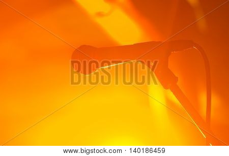 silhouette of wired microphone against orange concert gig background.