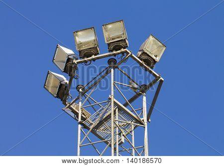 Few modern street lamps against blue sky.