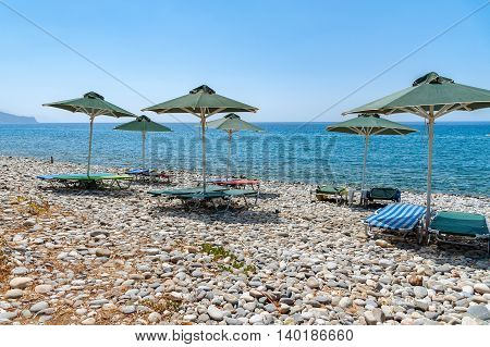Umbrellas and sunbeds at stony beach of Paleochora town on Crete island