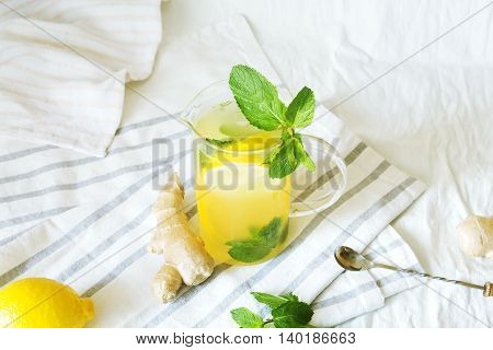 Lemonade with ginger and mint in kitchen. Home made ginger lemonade on striped napkin or towel. Healthy drink lemonade.