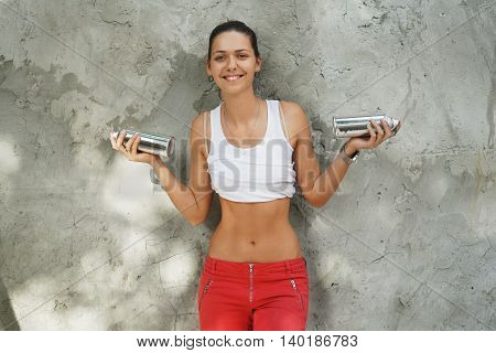 Shapely girl street artist with cans in their hands against the background of a gray wall in a white shirt and red pants .
