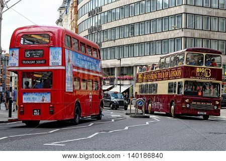 LONDON UK - JULY 1 2014: Red Routemaster Double Decker Bus (left) and a sightseeing bus (right) in the City of London. The old double-decker bus is one of the most iconic symbols of London.
