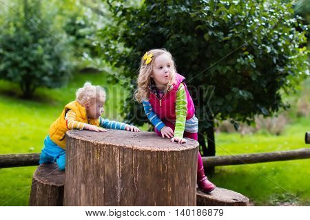 Little boy and girl climbing on a wooden playground in a park. Kids play outdoors on cold autumn day.