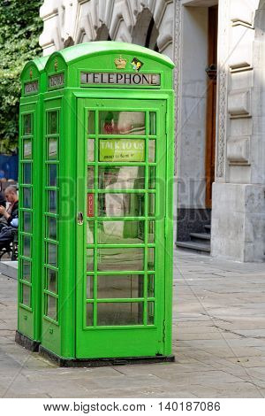 LONDON UK - JULY 1 2014: Two classic English phone boxes near bank station painted green. The traditional British red telephone box can also be seen in the British colonies.