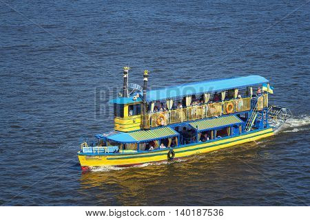 KIEV UKRAINE - JULY 24 2016: Closeup of a pleasure boat with people on board sailing at speed in Dnieper river Kiev Ukraine