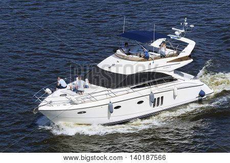 KIEV UKRAINE - JULY 24 2016: Closeup of a yacht with people on board sailing at high speed in Dnieper river Kiev Ukraine