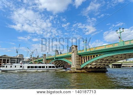 A cruise tourist boat passing under the Southwark bridge on the Thames river in London UK.