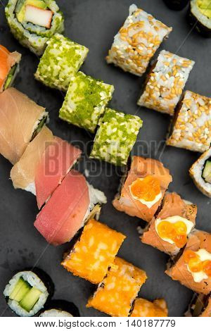 Sushi rolls on a black stone plate
