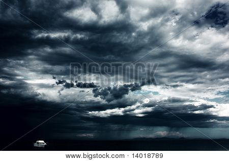 Alone white little boat on sea and dark storm clouds