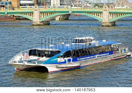 LONDON UNITED KINGDOM - JULY 1 2014: A City Cruises tour boat sails on the Thames River with Southwark bridge in the background. Thames is the longest river in England with 346 km in length.