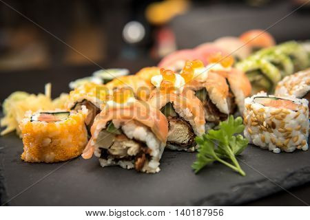 Sushi rolls on a black plate on stone plate