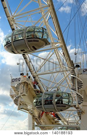 LONDON UK - JULY 1 2014: Tourists enjoy the view over the city in the capsules of the London Eye Europe's tallest Ferris wheel on the South Bank of the River Thames a famous tourist attraction.