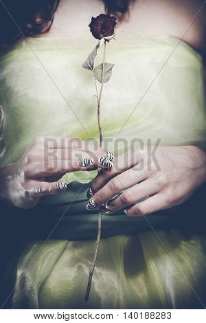 Romantic date gift nature loving young woman. Girl in light green dress hold small red rose.