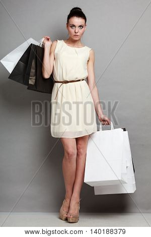 Woman in full length sale and retail concept. Girl with black and white shopping bags in hands on grey background in studio.