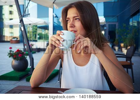 Portrait of beautiful young woman sitting in street cafe near modern business center and drinking coffee with thoughtful expression on her face