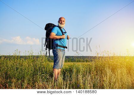 Portrait of smiling bearded aged man with rucksack standing in the field on a sunny day