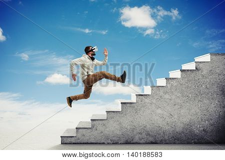 Side view of young bearded man in virtual reality glasses running violently up the grey stairs isolated over sky background