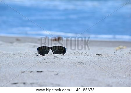Sunglasses Left Behind on Sandy Ocean Shore