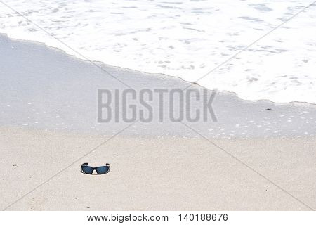 Sunglasses on Sand in the Ocean Tide