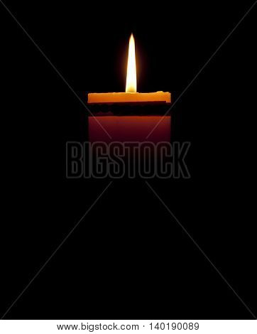 A small candle with black background in three quarters of the same