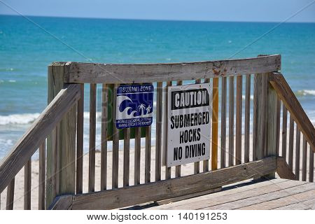 Tsunami Zone and No Diving Sign on Beach Boardwalk with Blue Ocean Background